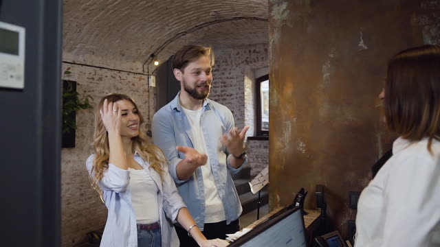 new arrival guests standing near reception in hotel and talking to the female manager which working at the desk - fare una prenotazione video stock e b–roll