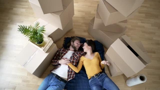 New Beginnings Young couple lying on the floor of their new house. young couple stock videos & royalty-free footage