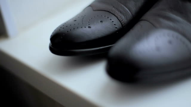 new black leather men's shoes on a white background. wedding day - scarpe video stock e b–roll