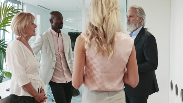 New Business CEO Conversing with Corporate Professionals Mature bearded entrepreneur discussing ideas with male and female professionals at kick-off party for new business. mid adult stock videos & royalty-free footage