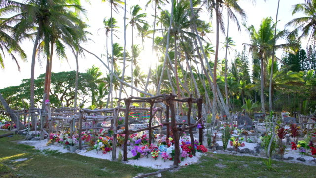 New Caledonia Maré Island Beach Cemetery Tropical Graveyard Maré Island colorful decorated Pacific Islander Beach Cemetery - Graveyard under tropical Palm Trees close to a dream beach against the sun close to dusk. 4K Real Time Video. Maré Island, Loyalty Islands, New Caledonia, Pacific Ocean Islands mare stock videos & royalty-free footage