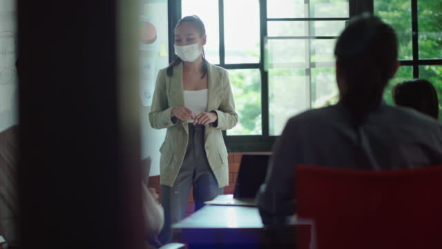 New concept of normal work in the office, Business woman wearing protective mask presenting on the board at a meeting in the office