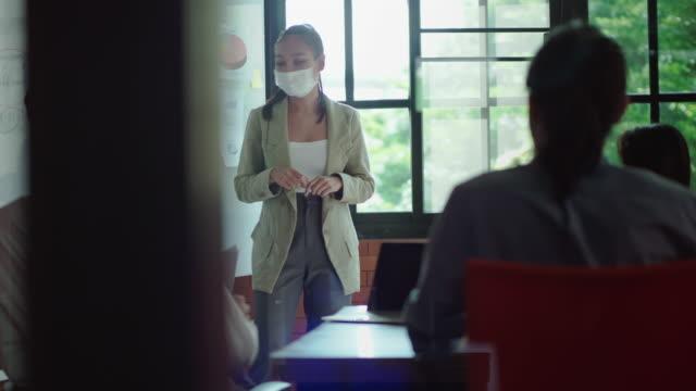 stockvideo's en b-roll-footage met nieuw concept van normaal werk in het bureau, bedrijfsvrouw die beschermend masker draagt dat op de raad bij een vergadering in het bureau aan de presentatie is - bedrijfsstrategie