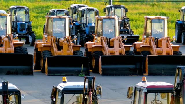 nya anläggningsmaskiner, bulldozrar och traktorer på parkeringen - excavator bildbanksvideor och videomaterial från bakom kulisserna