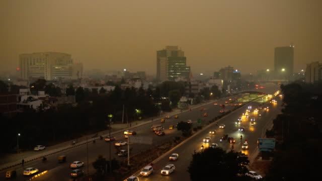 stockvideo's en b-roll-footage met de luchtmening van new delhi van avondverkeer in en uit straatpassage en verontreiniging aan de horizon - luchtvervuiling