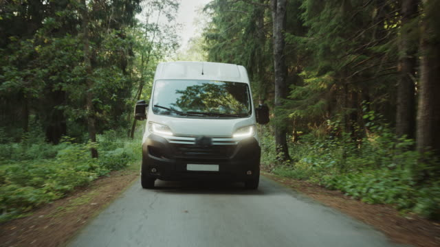 New Delivery Van / Truck Driving Through the Green Woods. Postal Delivery Service. Front View Following Shot New Delivery Van / Truck Driving Through the Green Woods. Postal Delivery Service. Front View Following Shot car transporter stock videos & royalty-free footage