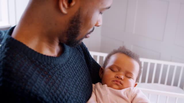 nya far gos sovande baby flicka i plantskolan hemma - baby sleeping bildbanksvideor och videomaterial från bakom kulisserna