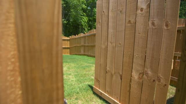 stockvideo's en b-roll-footage met nieuwe omheining poort opent te onthullen achtertuin - fence