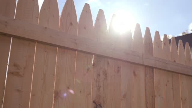 vídeos de stock e filmes b-roll de new fence tip move with sun flare close up - cercado