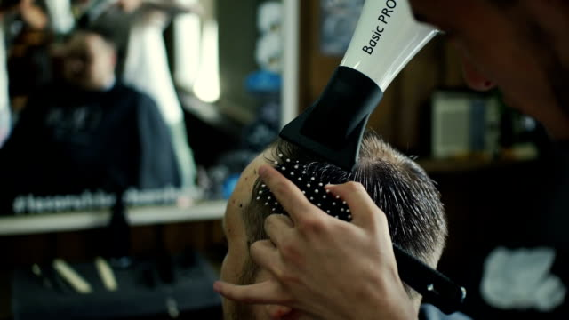 New hairstyle. Side view of young bearded man getting groomed at hairdresser with hair dryer while sitting in chair at barbershop video
