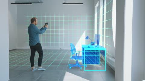 vidéos et rushes de new home office: modern interior designer utilise le logiciel de réalité augmentée sur l'ordinateur tablette numérique pour choisir, déplacer et manipuler des meubles 3d pour son studio de home office confortable. effets spéciaux vfx - bureau ameublement
