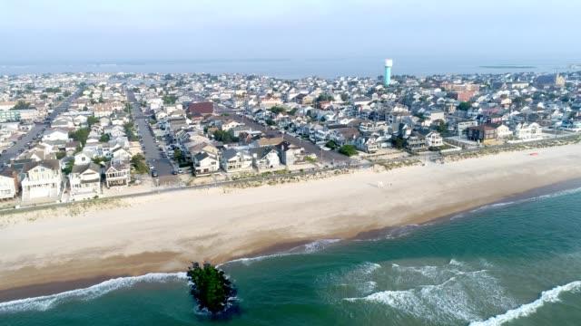 vidéos et rushes de ville de rivage du new jersey volant dedans de l'océan vers la baie - littoral