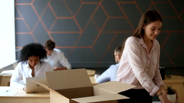 New job concept, young woman unpacking box on office desk video