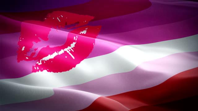 new lipstick lesbian pride flag rainbow flag video waving in wind. kiss lipstick lesbian flag background. lgbt rainbow pride labrys flag looping closeup 1080p hd 1920x1080 footage. rainbow pride concept flags footage video - kiss стоковые видео и кадры b-roll