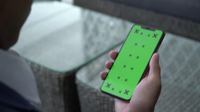 nuova schermata chiave chroma telefono cellulare sulla mano uomo d'affari - mano umana video stock e b–roll