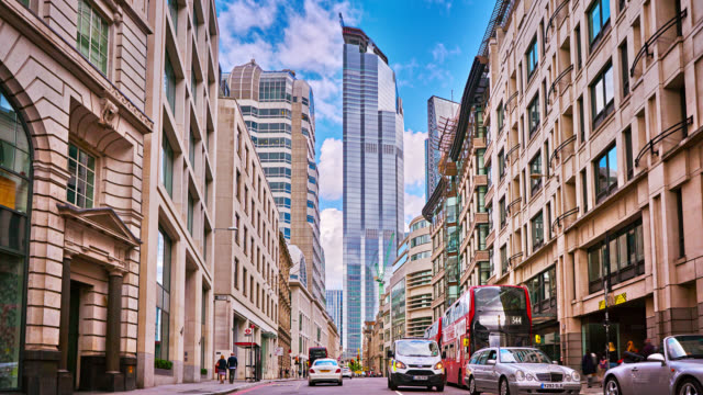New modern financial building and old residential structures. Cars traveling onto the camera. Clouds in the sunny sky. Happy scene, peaceful, city life. London, UK Cityscape, London, UK london architecture stock videos & royalty-free footage