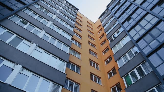 New modern residential building in the post soviet union country. Residential building exterior with yellow house facade and small balconies