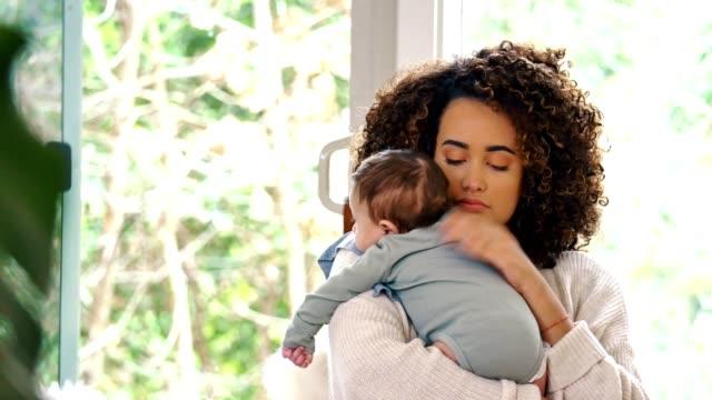 new mom burps her baby boy after a feeding - abbigliamento da neonato video stock e b–roll