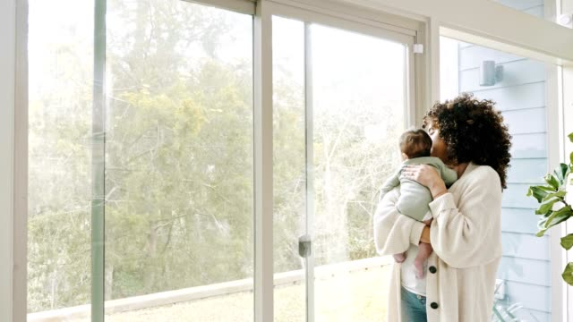 New mom looks through window while holding infant son