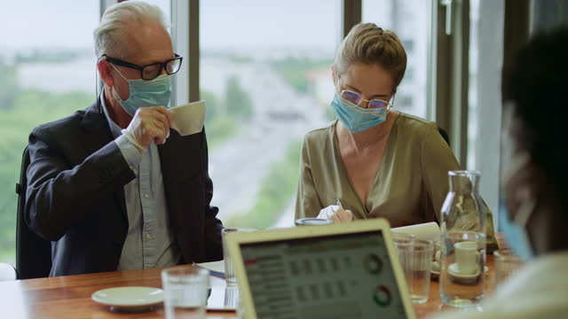 New normal. Diverse group of businesspeople wearing masks, busy in conference room Multi ethnic group of investors working on new strategy. Analyzing data on laptop. Wearing protective face masks. Post pandemic reality. financial planning stock videos & royalty-free footage