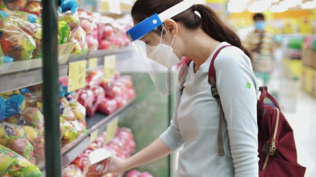 neues normales leben nach covid-19 virus, asiatische frau trägt gesichtsmaske und gesichtsschild einkaufen im supermarkt - supermarkt einkäufe stock-videos und b-roll-filmmaterial