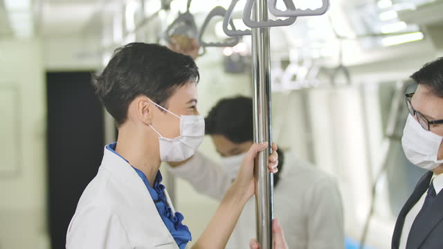 New normal lifestyle, Asian businessmen and colleagues or partners new type of greeting by touch elbows together while commuting on BTS or metro subway train wearing mask protection pandemic covid-19. Behavior in public places during