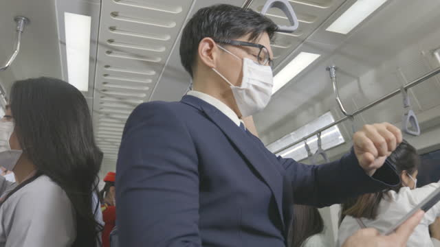 New normal lifestyle, Group of asians various professions get off BTS or metro subway wearing masks protection pollution and pandemic virus, keep distancing to prevent covid-19 while commuting on. Behavior in public places during disease outbreaks.