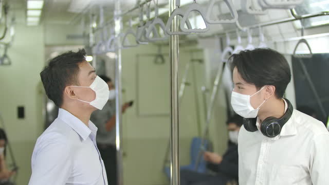 New normal lifestyle, Young asian man keep social distancing to prevent covid-19,new type of greeting by touching elbows together, wearing masks protection pandemic flu virus, while commuting on metro