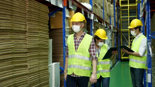 New normal people worker wearing protective mask working in a warehouse greeting to your coworker , working new normal concept
