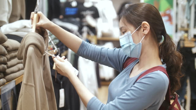 new normal shopping, asian woman shopping in clothing store with face mask - vendita al dettaglio video stock e b–roll