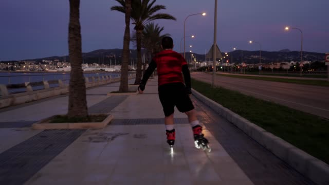 new normal situation: a man on a roller skates with lights in spain takes profit of the time allowed to do sport to skate with his roller skates with lights on their tires while the city is sleeping - new normal video stock e b–roll