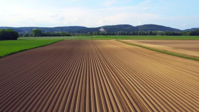neue gepflügtes kartoffelfeld und walhalla memorial im frühjahr - aerial view soil germany stock-videos und b-roll-filmmaterial