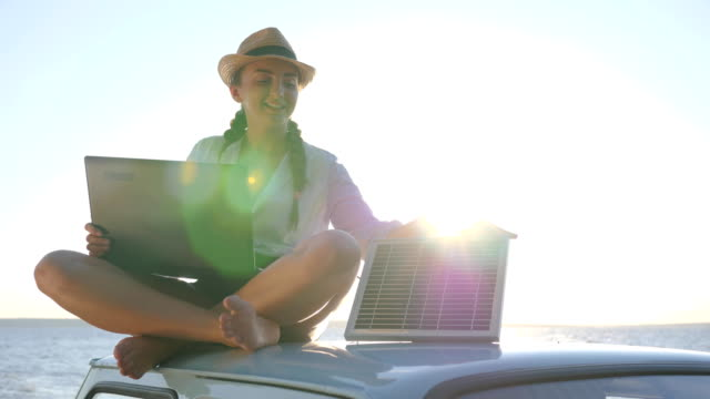new technology, happy girl sits on roof classic car with solar battery and laptop in hands in open air, female sitting on car video