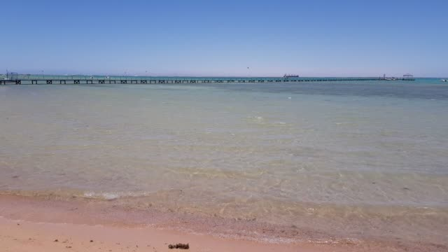 New wooden pier on the sea. boats are visible in the distance. video