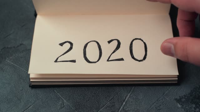 New Year 2020 is coming concept. Hand flips notepad or calendar sheet on table. 2019 is turning, 2020 is opening, top view video