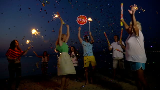 New Year party on the beach Slow motion clip of happy and excited people celebrating New Year or Christmas on the beach at night. They having fun and dancing with sparklers and confetti crackers petard stock videos & royalty-free footage