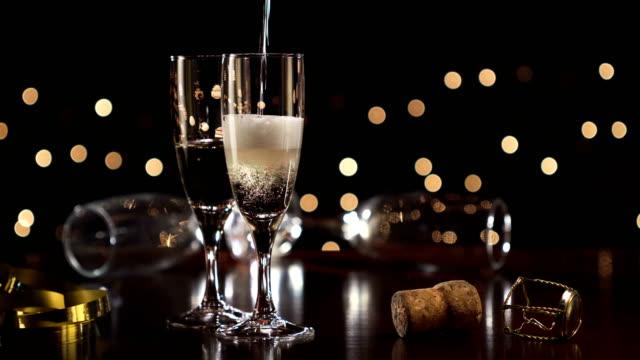 Champán del brindis de año nuevo, luces de Navidad fondo - vídeo