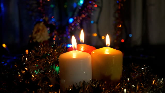New Year's candles, and Christmas decorations. Blurred background with colored lights. video