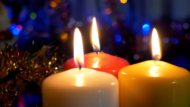 New Year's candles , and Christmas decorations. Blurred background with colored lights. Movement of the camera from the object video