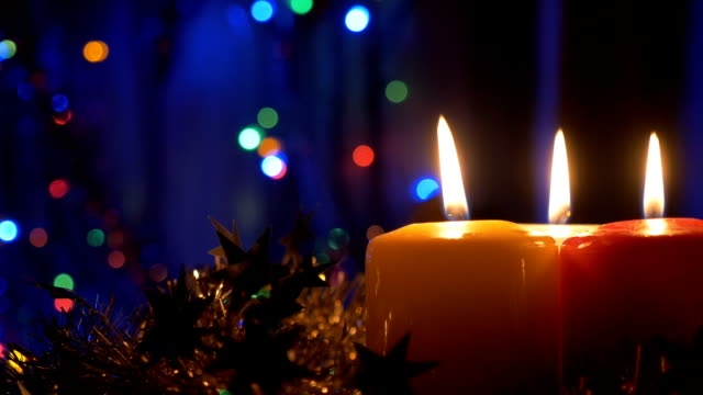 New Year's candles , and Christmas decorations. Blurred background with colored lights. The movement of the camera is closer to the object video