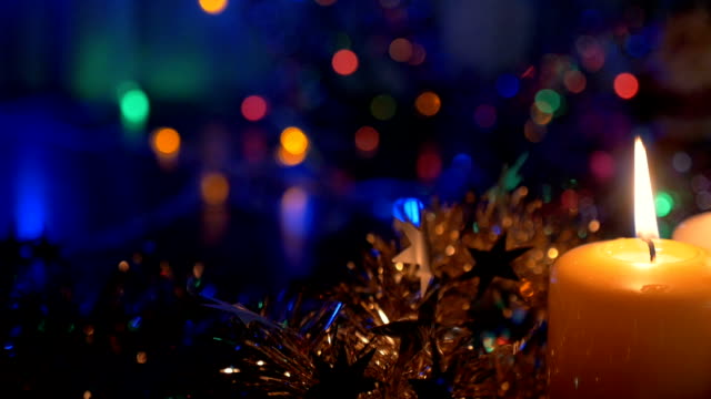 New Year's candles , and Christmas decorations. Blurred background with colored lights. video
