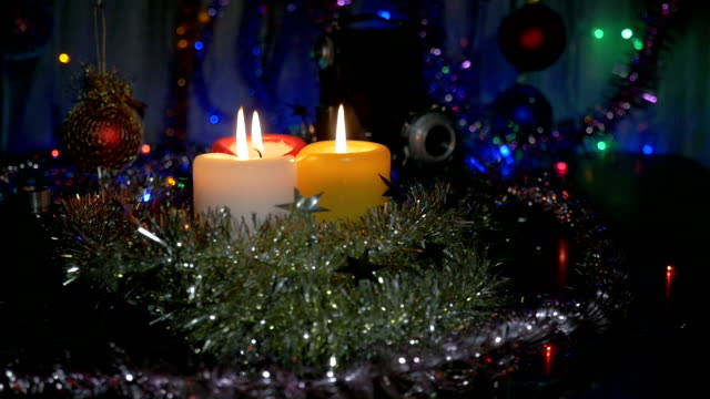 New Year's candles , and Christmas decorations. Blurred background with colored lights. Movement of the camera around the object video