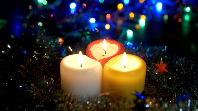 New Year's candles close-up , and Christmas decorations. Blurred background with colored lights. video