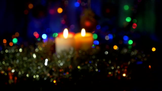 New Year's candles close-up. Blurred background with colored lights. Moving the camera from the non-focus area to the subject in focus. video