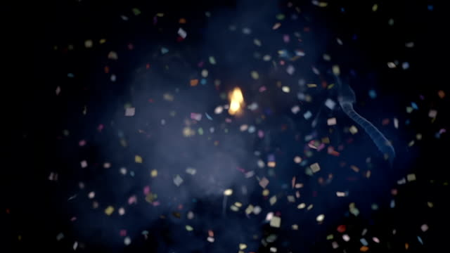 New Year's cracker exploded powerfully and a cloud of confetti fly away in smoke New Year's cracker exploded powerfully and a cloud of confetti fly away in smoke on black background. Slow motion. High speed camera petard stock videos & royalty-free footage