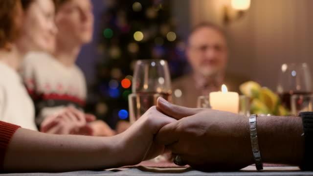 cena di capodanno. famiglia che prega davanti al cibo tenendosi per mano. - christmas table video stock e b–roll