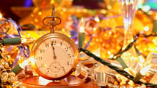 New Year's Eve holiday party with champagne, disco ball, decorations. New Year's Eve celebration party with champagne, glasses, disco ball, decorations including beads, lights, blow horns and confetti.  Old clock pocket watch counts down the time. new year's eve stock videos & royalty-free footage