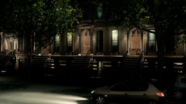 New York City brownstone homes and cars at night - video