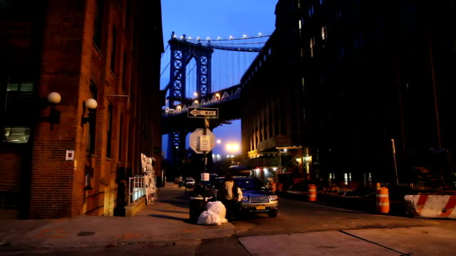 New York, Manhattan Bridge , DUMBO The Manhattan bridge by night, at the corner Main Street, Water Street, in DUMBO, Brooklyn. A Jogger, a woman and a blink car light. manhattan bridge stock videos & royalty-free footage