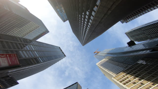 new york, usa. upward view of city skyline buildings with sky. wide angle pov from the road. 28_ny_38 - skyscrapers stock videos & royalty-free footage